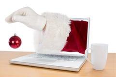 La imagen compuesta de la mano de santas está sosteniendo un bulbo de la Navidad Imagen de archivo libre de regalías