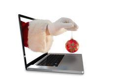 La imagen compuesta de la mano de santas está sosteniendo un bulbo de la Navidad Imagen de archivo