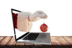 La imagen compuesta de la mano de santas está sosteniendo un bulbo de la Navidad Fotos de archivo libres de regalías