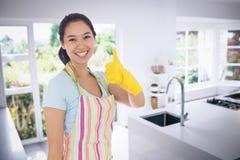 La imagen compuesta de la mujer en la limpieza viste el donante de los pulgares para arriba Foto de archivo libre de regalías