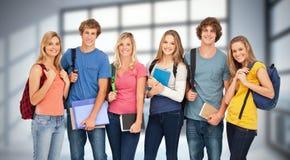 La imagen compuesta de los estudiantes sonrientes que llevan las mochilas y que se sostienen reserva en sus manos Imagen de archivo