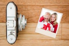 La imagen compuesta de los socios sonrientes de la cubierta de la mujer observa y del regalo de la tenencia Foto de archivo