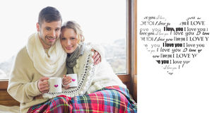 La imagen compuesta de pares cariñosos en invierno lleva con las tazas contra ventana Imágenes de archivo libres de regalías