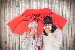 La imagen compuesta de pares en invierno forma el estornudo debajo del paraguas Imagen de archivo