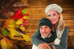 La imagen compuesta de pares felices en invierno forma el abarcamiento Imagen de archivo libre de regalías