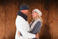 La imagen compuesta de pares felices en invierno forma el abarcamiento Imagenes de archivo