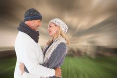 La imagen compuesta de pares felices en invierno forma el abarcamiento Imagen de archivo