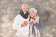 La imagen compuesta de pares felices en invierno forma sostener las tazas Fotografía de archivo libre de regalías