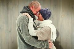 La imagen compuesta de pares maduros felices en invierno viste el abarcamiento Imagen de archivo libre de regalías