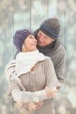 La imagen compuesta de pares maduros felices en invierno viste el abarcamiento Fotos de archivo libres de regalías