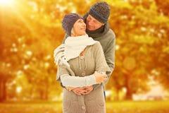 La imagen compuesta de pares maduros felices en invierno viste el abarcamiento Foto de archivo