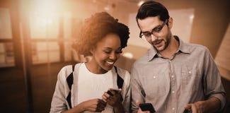 La imagen compuesta de 2 personas sonrientes está utilizando el teléfono móvil Imagen de archivo libre de regalías