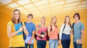 La imagen compuesta de un grupo de estudiantes universitarios que se colocan como una muchacha se coloca delante de ellos Imagenes de archivo