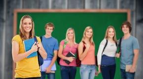 La imagen compuesta de un grupo de estudiantes universitarios que se colocan como una muchacha se coloca delante de ellos Fotografía de archivo libre de regalías