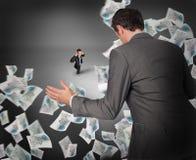La imagen compuesta del hombre de negocios que presenta con distribuye con el hombre de negocios minúsculo Fotos de archivo libres de regalías