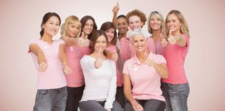 La imagen compuesta del retrato de los amigos femeninos que muestran thums sube la muestra para la conciencia del cáncer de pecho fotos de archivo libres de regalías