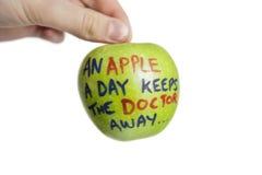 La imagen cosechada de la mano que sostiene una manzana del granny smith con refranes manda un SMS sobre el fondo blanco Imagenes de archivo