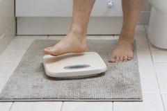 La imagen cosechada de los pies del hombre que caminan encendido pesa la escala fotos de archivo