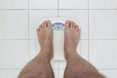 La imagen cosechada de los pies del hombre que se colocan encendido pesa la escala imagen de archivo