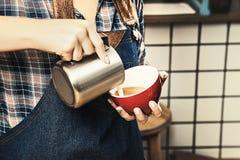 La imagen cosechada del barista femenino atractivo celebra la taza de latte en una cafetería del escandinavo-estilo imagen de archivo libre de regalías
