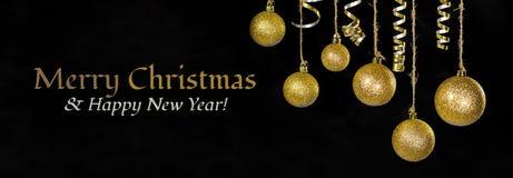 La imagen de la decoración festiva de la bola del oro del árbol de la Navidad delante del fondo negro allí es la feliz Navidad de Fotos de archivo libres de regalías