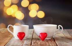 La imagen de dos chocolates rojos de la forma del corazón y las tazas de los pares de café en la tabla de madera delante del boke Fotografía de archivo libre de regalías