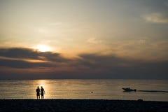 La imagen de dos personas en amor en la puesta del sol Imagen de archivo