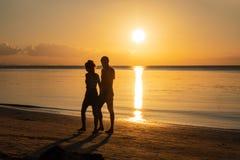 La imagen de dos personas en amor en la puesta del sol concepto del recorrido imagen de archivo