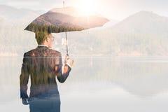 La imagen de la exposición doble de los hombres de negocios está separando el paraguas durante la salida del sol cubierta con ima fotografía de archivo