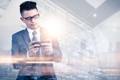 La imagen de la exposición doble de usar del hombre de negocios o un smartphone o juega a un juego durante la salida del sol cubi imágenes de archivo libres de regalías