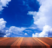 La imagen de fondo borrosa de la superficie de madera marrón vacía de la tabla y del cielo azul, para el montaje de la exhibición Fotografía de archivo libre de regalías