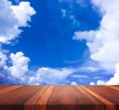 La imagen de fondo borrosa de la superficie de madera marrón vacía de la tabla y del cielo azul, para el montaje de la exhibición Imagenes de archivo