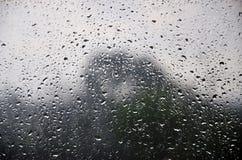 La imagen de fondo de la lluvia cae en una ventana de cristal Foto macra con la profundidad del campo baja imagen de archivo libre de regalías