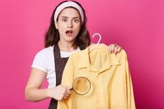 La imagen de la hembra chocada lleva la camiseta blanca, delantal marrón y banda del pelo, sostiene la camisa amarilla y la lupa  imagen de archivo libre de regalías