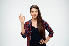 La imagen de la chica joven hace gesto aceptable y vestida en camisa de tela escocesa Fotos de archivo