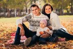 La imagen de la familia preciosa en el parque del otoño, padres jovenes con los niños adorables agradables que juegan al aire lib Imágenes de archivo libres de regalías