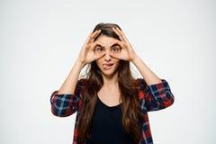 La imagen de la muchacha divertida joven hace gesto aceptable y vestida en camisa de tela escocesa Imágenes de archivo libres de regalías