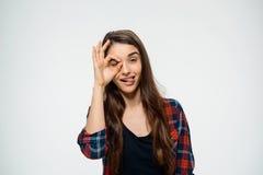 La imagen de la muchacha divertida joven hace gesto aceptable y vestida en camisa de tela escocesa Foto de archivo libre de regalías