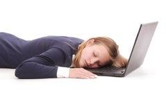 La imagen de la muchacha durmiente joven linda miente cerca del ordenador portátil Fotografía de archivo