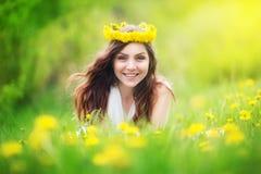 La imagen de la mujer bonita que se acuesta en los dientes de león coloca, che feliz Fotos de archivo