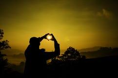 La imagen de la silueta un hombre crea símbolo del amor con la mano foto de archivo