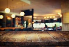 La imagen de la tabla de madera delante del extracto empañó el fondo de las luces del restaurante Imagenes de archivo