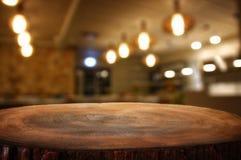 La imagen de la tabla de madera delante del extracto empañó el fondo de las luces del restaurante Fotos de archivo libres de regalías