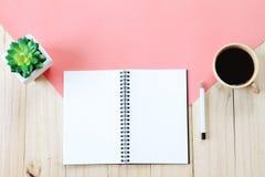 La imagen de la visión superior del cuaderno abierto con las páginas en blanco, los accesorios y la taza de café en fondo de made Fotos de archivo libres de regalías