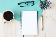 La imagen de la visión superior del cuaderno abierto con las páginas en blanco y la taza de café en fondo de madera, alista para  Foto de archivo