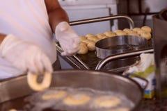 La imagen de las manos de los hombres del cocinero El proceso de cocinar los anillos de espuma imagen de archivo