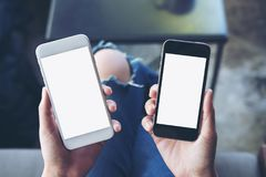 La imagen de la maqueta de un ` s de la mujer da sostener dos teléfonos móviles con la pantalla blanca en blanco Fotografía de archivo libre de regalías