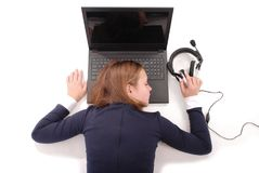 La imagen de la muchacha durmiente joven linda miente cerca del ordenador portátil en auriculares Imágenes de archivo libres de regalías