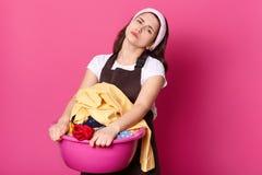 La imagen de la mujer europea trastornada sostiene el lavabo con ropa sucia, lleva el delantal marrón, ha trastornado expresiones fotografía de archivo libre de regalías
