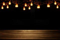 La imagen de la tabla de madera delante del extracto empañó el fondo de las luces del restaurante Foto de archivo libre de regalías